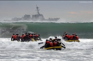 Navy Seals in training participate in surf passage.
