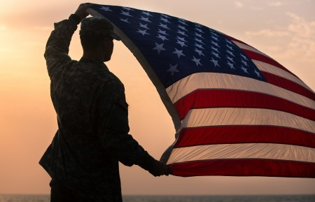 Spc. Morgan Austin, communications specialist with Joint Forces Command – United Assistance, assigned to Headquarters and Headquarters Battalion, 101st Airborne Division (Air Assault), holds up the U.S. flag during a promotion and re-enlistment ceremony Jan. 1, 2015, at Barclay Training Center, Monrovia, Liberia. United Assistance is a Department of Defense operation in Liberia to provide logistics, training and engineering support to U.S. Agency for International Development-led efforts to contain the Ebola virus outbreak in western Africa. (U.S. Army photo by Spc. Rashene Mincy, 55th Signal Company (Combat Camera)/ Released)